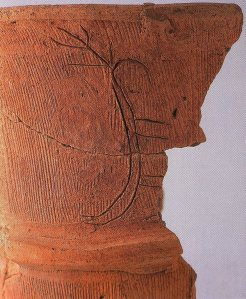 Abstract carving of human figure in feathered headdress on pottery. East Nagatoro ruins