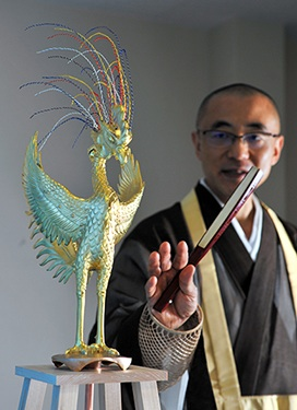 Monsho Kamii, the head priest at Byodoin temple in Uji, Kyoto Prefecture, shows a phoenix replica with a five-colored crest. (Noboru Tomura)