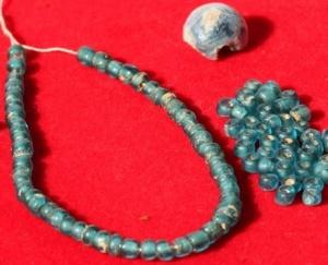 A glass ball and beads unearthed at the Takamatsuzuka tombs in Asuka, Nara Prefecture (Asahi Shimbun file photo)